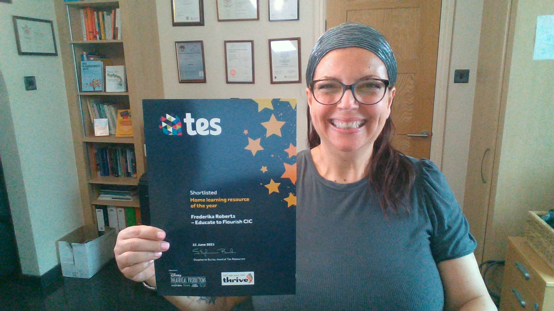 The image shows Educate to Flourish's Founder, Frederika Roberts, in her home office.  She is smiling broadly and holding a certificate stating the resource she created was shortlisted for the TES Home Learning Resource of the Year Award 2021.